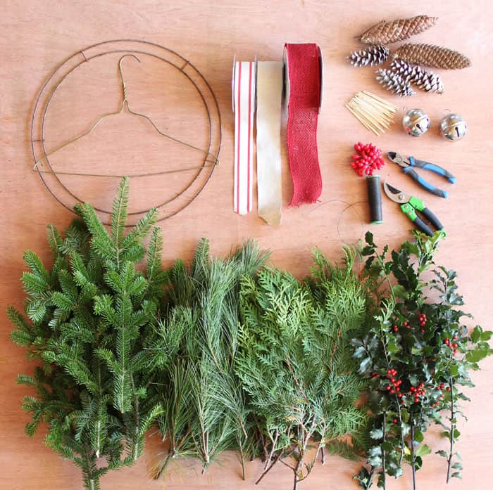 Wreath Making supplies | Christmas Wreath by popular Canada DIY blog, Fynes Designs: flatlay image of a wire hanger, red and white ribbon, pinecones, silver bells, tooth picks, holly berries, wire cutters, wire spool, wire ring, and various pine tree boughs.
