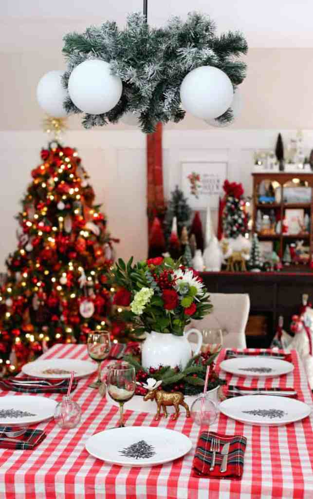 Christmas Home Decor Tour featured by top US design blog, Fynes Designs: Red themed dining room Christmas decorations | Holiday Home Decor Tour 2019 by popular Nova Scotia life and style blog, FYNE Designs: image of a dining room with a Christmas tree with red ornaments and a table with a red plaid table cloth.