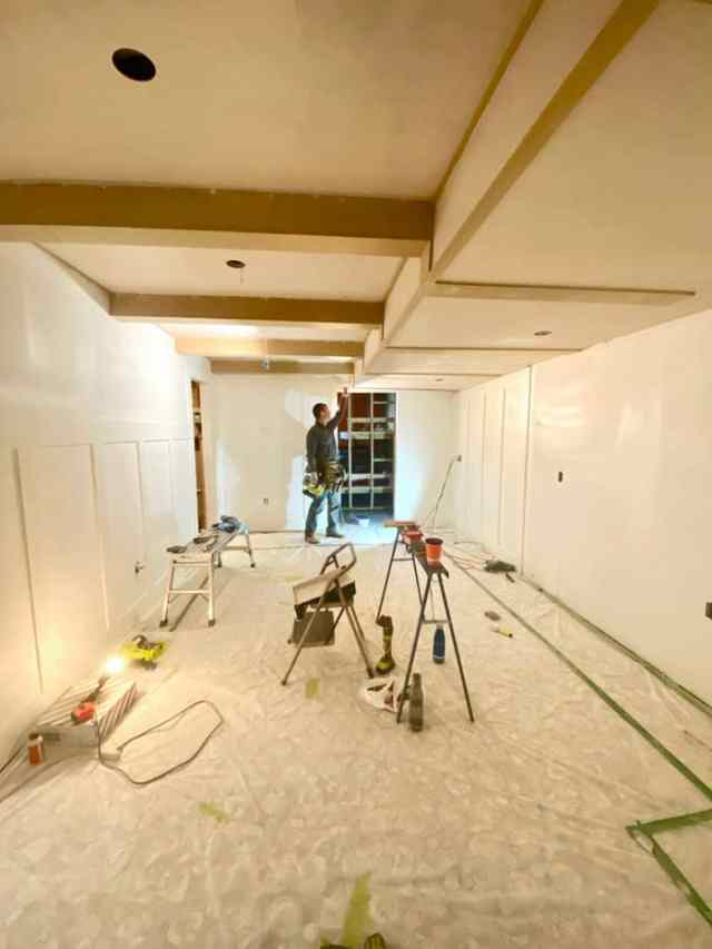 Faux ceiling beams   Jeffrey Court by popular US interior design blog, Fynes Designs: image of a basement with a white board and batten wall and faux beams.