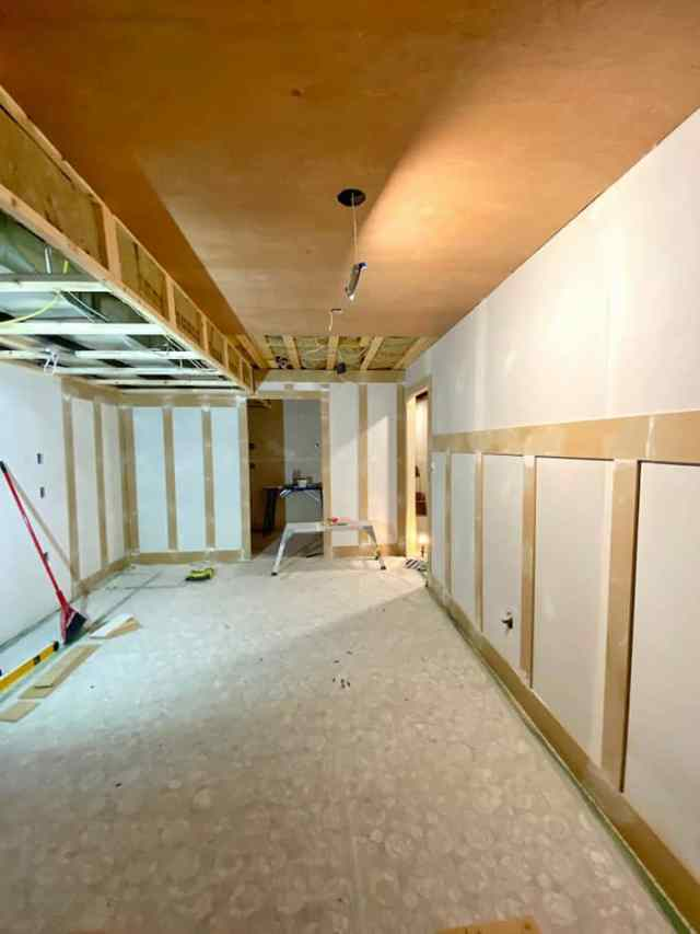 MDF and Meranti to cover basement drywall and ceiling | Jeffrey Court by popular US interior design blog, Fynes Designs: image of a basement with a board and batten wall.