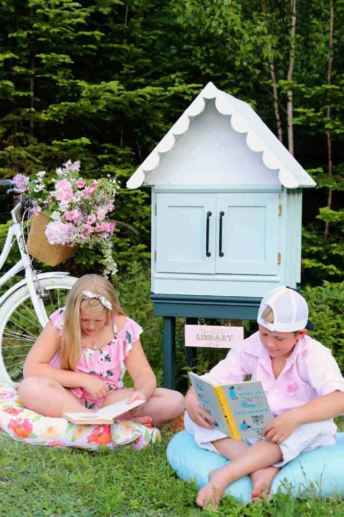 How to build a free little library | Little Free Library Plans by popular US DIY blog, Fynes Designs: image of a free little library next to a beach cruiser bike with a wicker basket full of pink flowers and children sitting on floor pillows while looking at books.