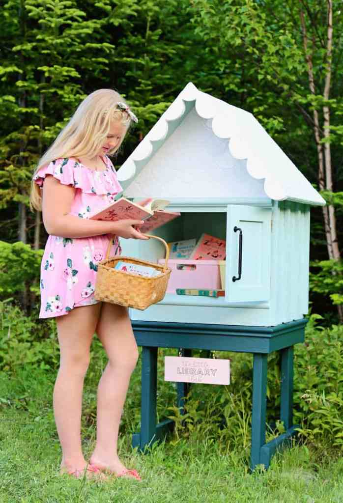How to build a DIY Little Free Library from a old cabinet | Little Free Library Plans by popular US DIY blog, Fynes Designs: image of a young girl holding a wicker basket and looking at a book in a free little library.