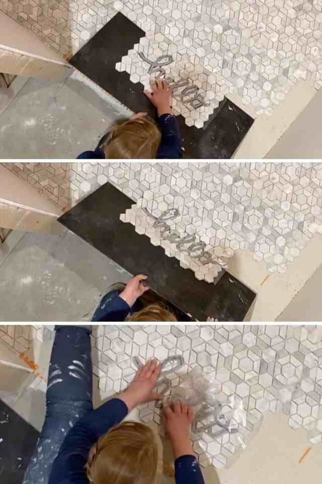 how to put a phrase in tile flooring | Tile Lettering by popular US interior design blog, Fynes Designs: image of hello tile lettering being placed on a tile floor.