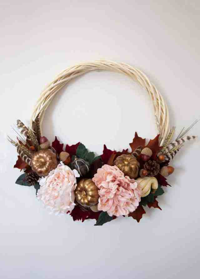 Beautiful fall wreath tutorial to make with soft pinks and gold |  Fall Wreath by popular Canada DIY blog, Fynes Designs: image of a fall wreath made with faux pink flowers, feather, faux leaves, Styrofoam pumpkins, and Styrofoam acorns.