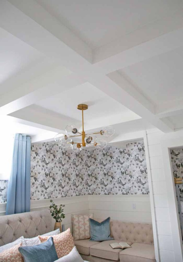 Coffered basement ceiling for less than $100! | Master Bedroom Design by popular Canada interior design blog, Fynes Designs: image of a bedroom with floral wall paper, vinyl plank flooring, modern light fixture, tuft bench, and tufted bed frame.