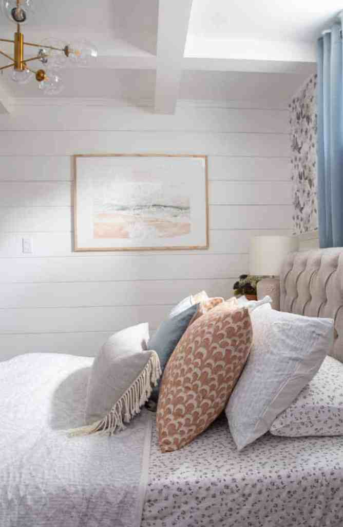 Create a stunning basement master bedroom with these ideas | Master Bedroom Design by popular Canada interior design blog, Fynes Designs: image of a bedroom with floral wall paper, shiplap walls, blue curtains, modern light fixture, tuft bench, and tufted bed frame.