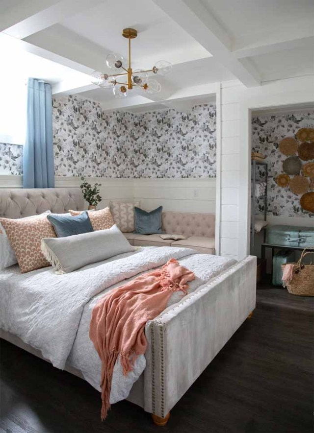 Basement vacation rental master bedroom | Master Bedroom Design by popular Canada interior design blog, Fynes Designs: image of a bedroom with floral wall paper, modern light fixture, tuft bench, and tufted bed frame.