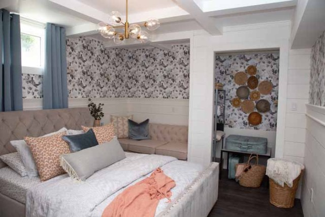 Master bedroom in a basement vacation rental | Master Bedroom Design by popular Canada interior design blog, Fynes Designs: image of a bedroom with floral wall paper, modern light fixture, tuft bench, and tufted bed frame.