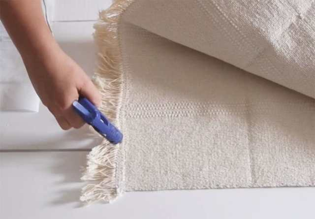 Glue the sides of the rug | Boho Pillows by popular Canada DIY blog, Fynes Designs: image of a woman using a hot glue gun and making a boho pillow out of a IKEA Sortso rug.
