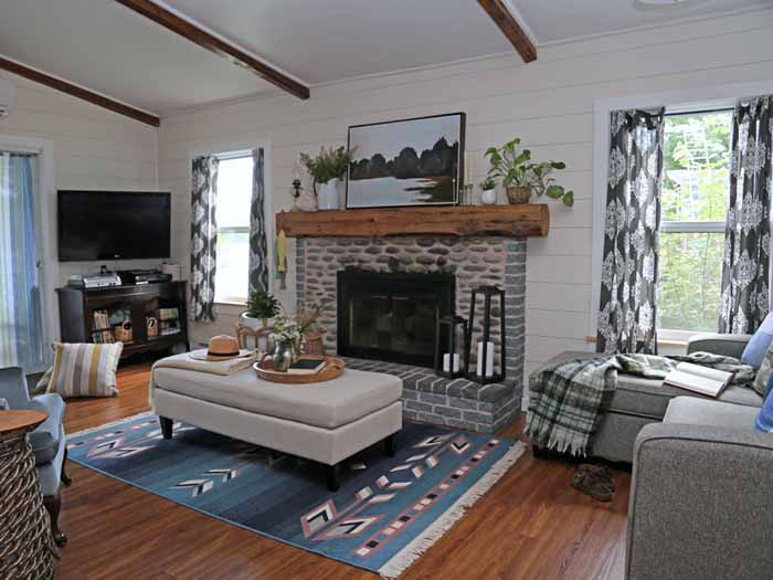 Farmhouse Cottage by popular Canada DIY blog, Fynes Designs: image of a farmhouse cottage living room decorated with blue armchairs, gray sectional couch, black bookshelves, blue accent rug, grey and white curtains, and cream ottoman.