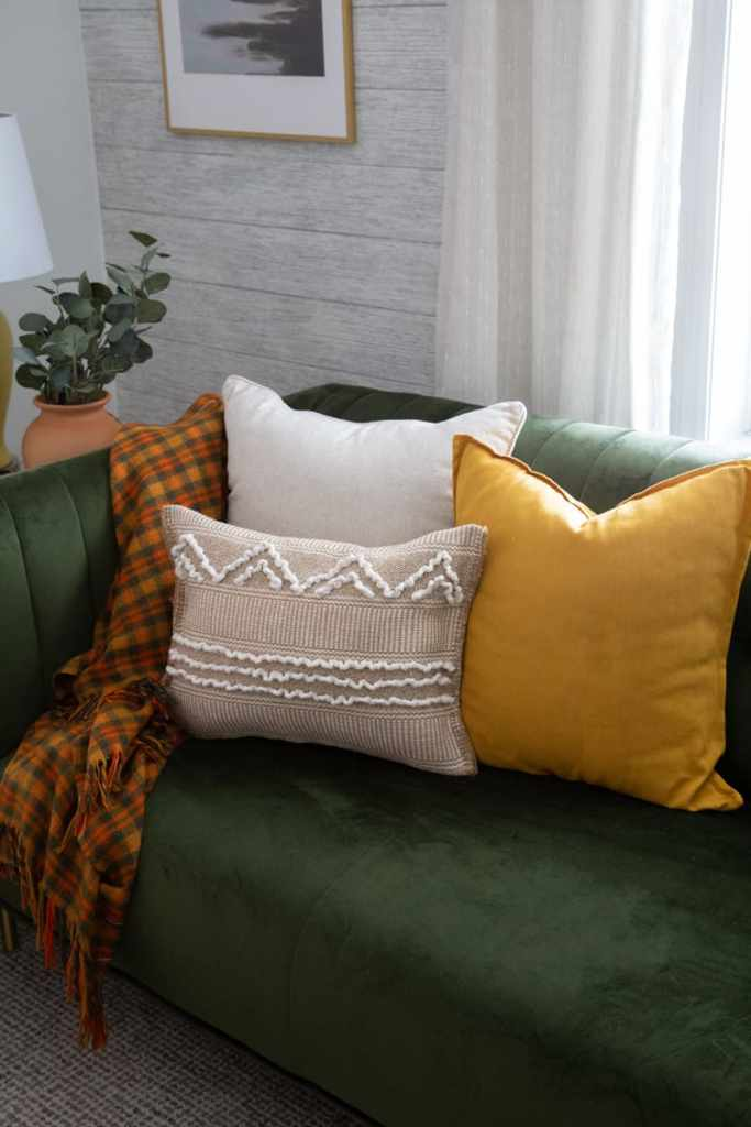 IKEA HACKS: boho pillows from $3 rugs! |  Boho Pillows by popular Canada DIY blog, Fynes Designs: image of various boho pillows on a green velvet couch.