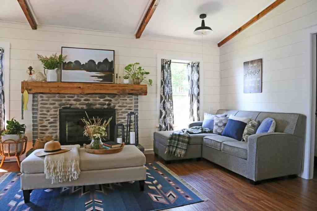 Farmhouse cottage living room makeover with a rock wall fireplace |Farmhouse Cottage by popular Canada DIY blog, Fynes Designs: image of a farmhouse cottage living room decorated with blue armchairs, gray sectional couch, black bookshelves, blue accent rug, grey and white curtains, and cream ottoman.