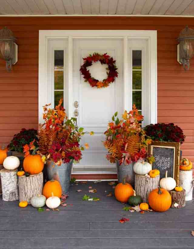 Budget friendly fall porch decorating ideas | Fall Front Porch Ideas by popular Canada life and style blog, Fynes Designs: image of a front porch decorated with tree stumps, pumpkins, dark red mums and tin buckets filled with tree branches containing orange, red, and yellow leaves.