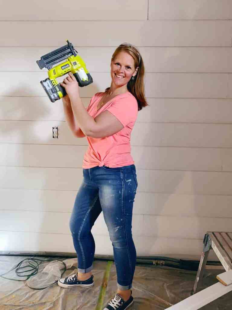 Putting up Shiplap on basement walls |Shiplap Wall by popular Canada interior design blog, Fynes Designs: image of a woman holding a nail gun in front of a shiplap wall.