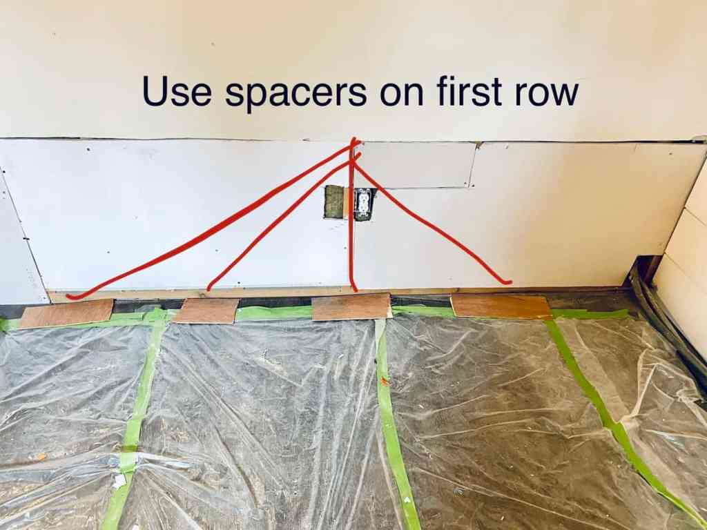 use spacers on the first row before putting up first row of shiplap |Shiplap Wall by popular Canada interior design blog, Fynes Designs: image of a basement floor covered in plastic.