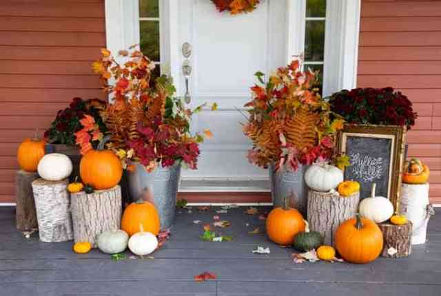 Fall Porch decorating ideas with natural elements | Fall Front Porch Ideas by popular Canada life and style blog, Fynes Designs: image of a front porch decorated with tree stumps, pumpkins, dark red mums and tin buckets filled with tree branches containing orange, red, and yellow leaves.