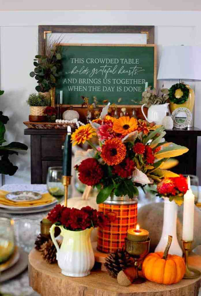 Farmhouse thanksgiving dining room decor |Thanksgiving decor by popular Canada interior design blog: image of This crowded table chalkboard sign on a dresser decorated with glass bottles, black jars with flowers in them, yellow base lamp, white ceramic pitcher, yellow cloth napkins, faux green plants, and a table set with green wine glasses, white plates, yellow napkins, red and white plates, a basket full of rolls, pinecones, and a vase filled with yellow and red daisies.