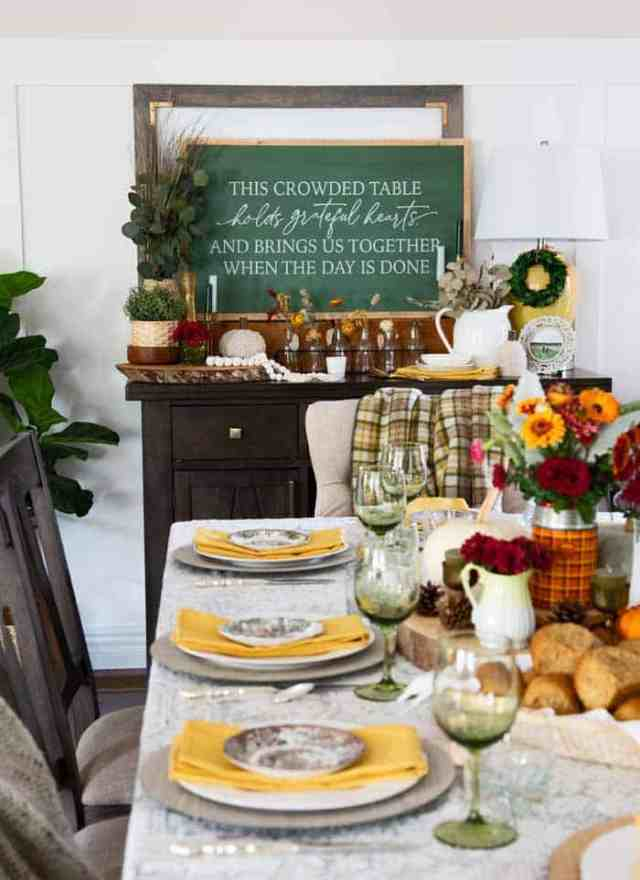 Thanksgiving dining room decor |Thanksgiving decor by popular Canada interior design blog: image of This crowded table chalkboard sign on a dresser decorated with glass bottles, black jars with flowers in them, yellow base lamp, white ceramic pitcher, yellow cloth napkins, faux green plants, and a table set with green wine glasses, white plates, yellow napkins, red and white plates, a basket full of rolls, pinecones, and a vase filled with yellow and red daisies.