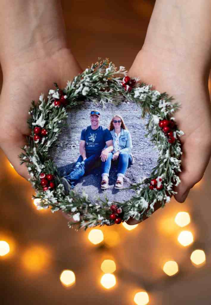 Easy to make keepsake photo ornaments from IKEA coasters | Photo Ornament by popular Canada DIY blog, Fynes Designs: image of a woman holding a mini Christmas wreath photo ornament.