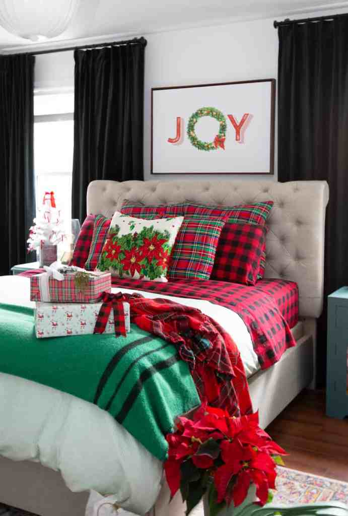 Christmas decorating ideas for the bedroom |Colorful Christmas Decorations by popular Canada Interior Design blog, Fynes Designs: image of a bed with made with Christmas bedding.
