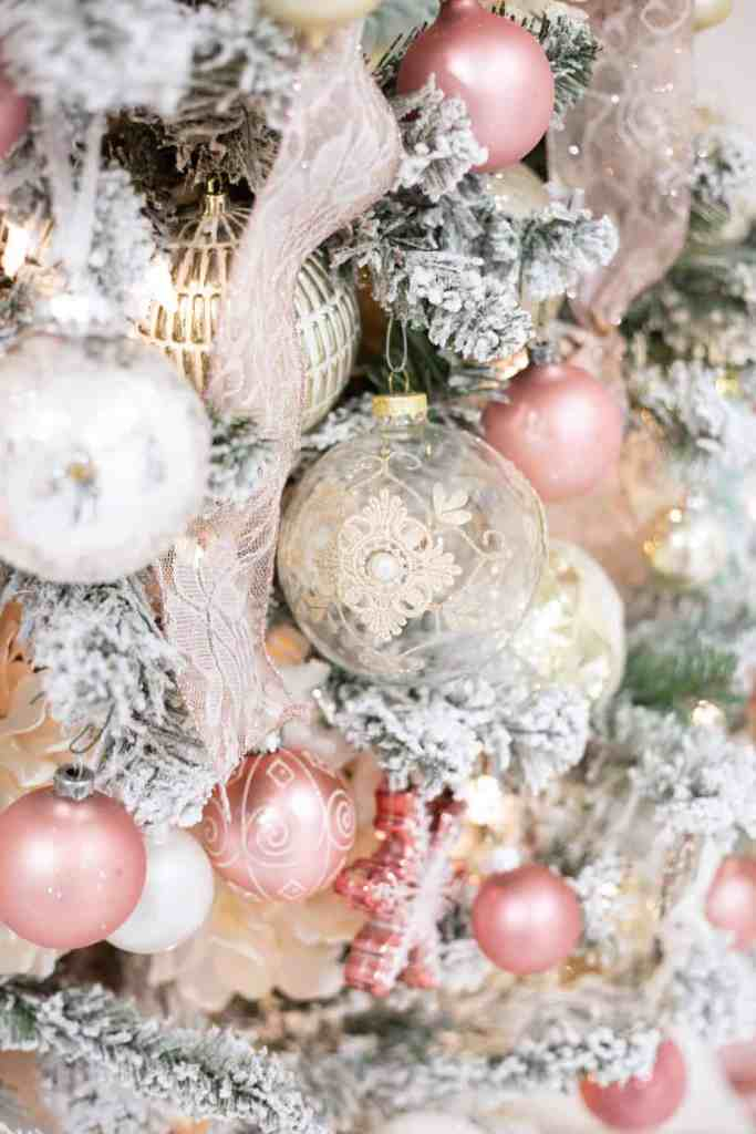 Step by Step instructions how to decorate a Christmas tree |How to Decorate a Christmas Tree with Ribbon by popular Canada DIY blog, Fynes Designs: image of a flocked Christmas tree decorated with pink ribbon and pink, gold, rose gold, light blue and white ornaments.