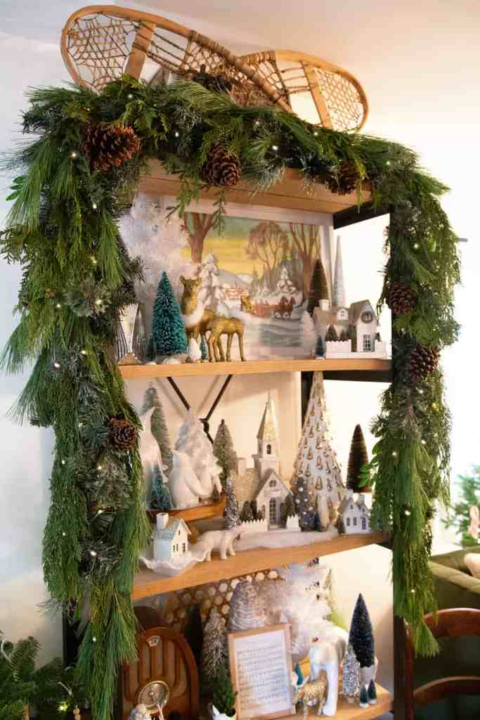 Add fresh garland to your Christmas shelves |How to Hang Garland by popular Canada DIY blog, Fynes Designs: image of garland hanging on a shelf decorated with various Christmas decor items.