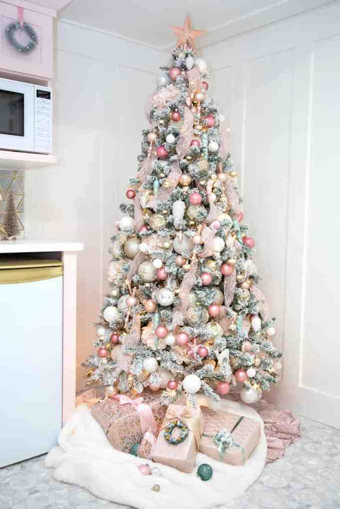 Designer tips how to decorate a Christmas tree with Ribbon |How to Decorate a Christmas Tree with Ribbon by popular Canada DIY blog, Fynes Designs: image of a flocked Christmas tree decorated with pink ribbon and pink, gold, rose gold, light blue and white ornaments.