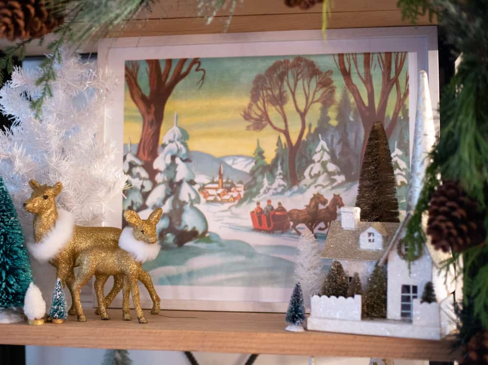Sleigh ride Christmas printable  How to Hang Garland by popular Canada DIY blog, Fynes Designs: image of a sleigh ride Christmas print, gold glitter reindeer, and bottle brush trees.