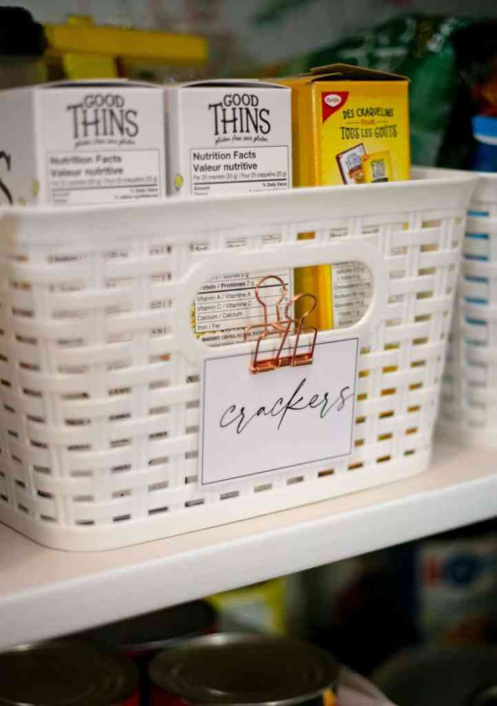 Free kitchen pantry labels from Fynes Designs |Pantry Organization Tips by popular Canada interior design blog, Fynes Designs: image of a white plastic basket with a modern label attached to it.
