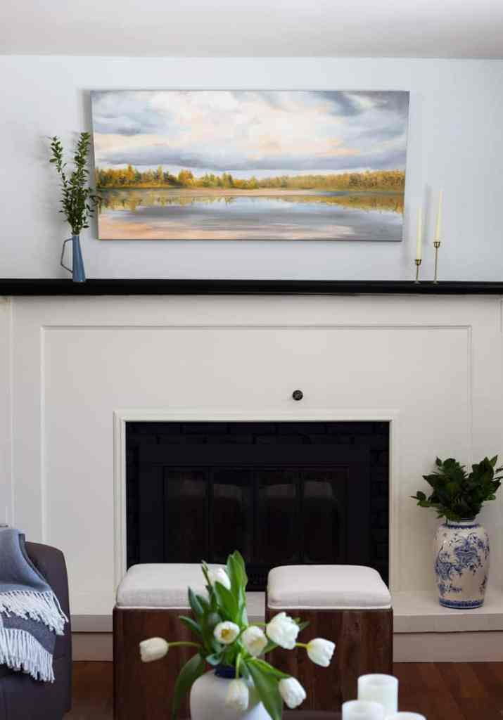 landscape art to create sense of movement in a space above an updated fireplace |Living Room Makeover by popular Canada life and style blog, Fynes Designs: image of a living room with a white fireplace, grey recliner chair, cream color couch, blue and white throw pillows, light blue rug, round wooden coffee table, and landscape painting hanging above the fireplace mantle.