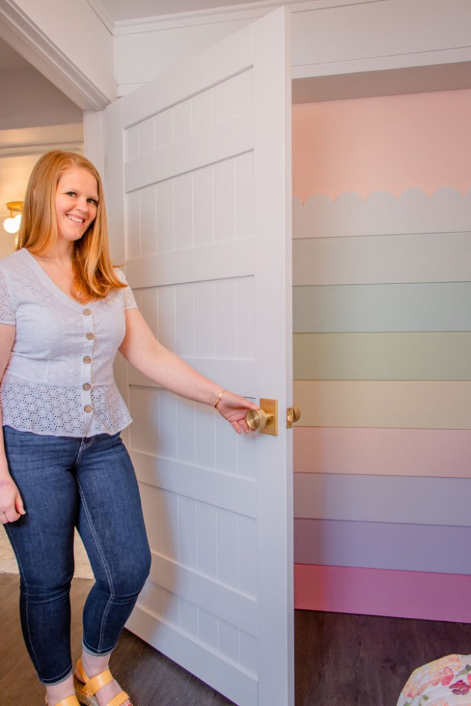 Rainbow Shiplap wall from Fynes Designs |  Bunk Room Ideas by popular Canada home design blog, Fynes Designs: image of a woman walking in to a rainbow shiplap wall.