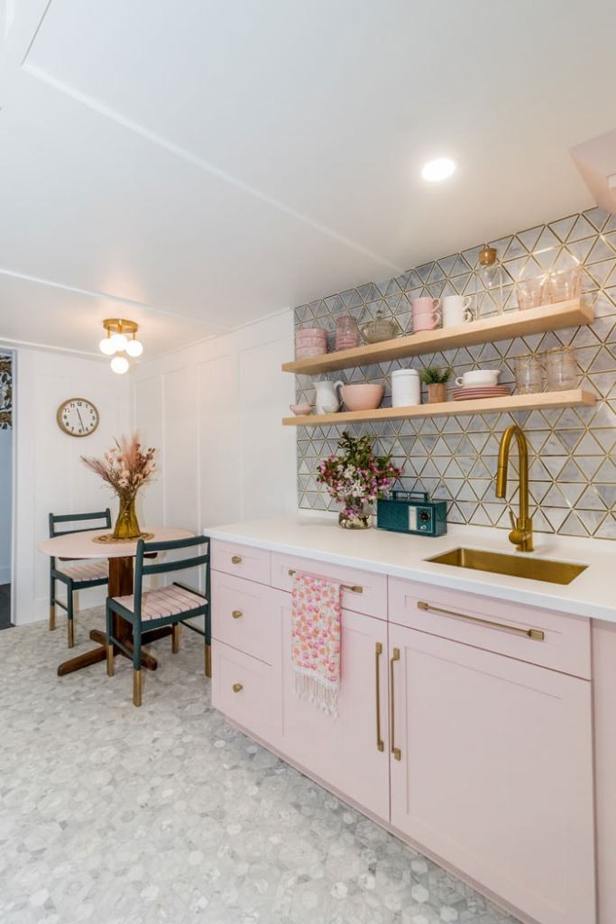 Basement Kitchenette ideas |  Bunk Room Ideas by popular Canada home design blog, Fynes Designs: image of a basement kitchen with a marble triangle backsplash, marble tile flooring, pink cabinets, gold sink, gold faucet, floating wood shelves, and white and green table.