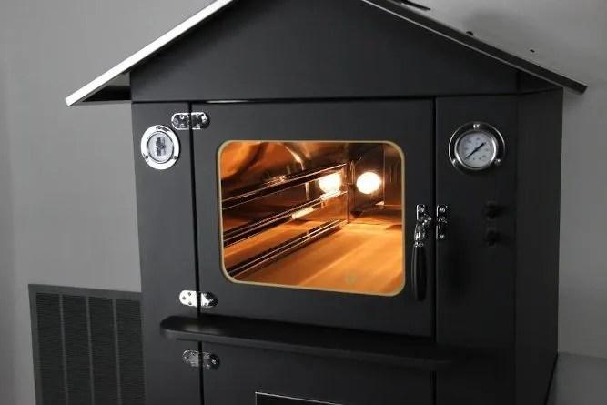 forno da esterno di colore nero con tetto in acciao inox presente luci e ventilazione accese