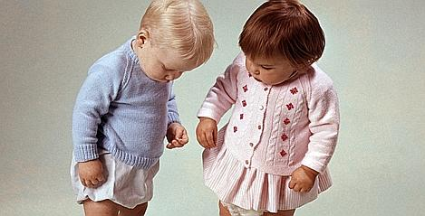 Classic Collection, Page 122, 10420816, Two little children, in a studio shot, little girl dressed in a pink cardigan, little boy dressed in a blue cardigan, both looking at something on the floor, 1967  (Photo by Popperfoto/Getty Images)