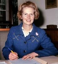 Un costum albastru cu detalii de lant si o brosa discreta, o floare