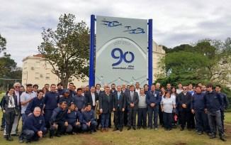 El ministro de defensa Oscar Aguad y Ercole Felippa posan junto a varios operarios de la fábrica frente a un cartel conmemorativo del 90 aniversario (foto: FAdeA).