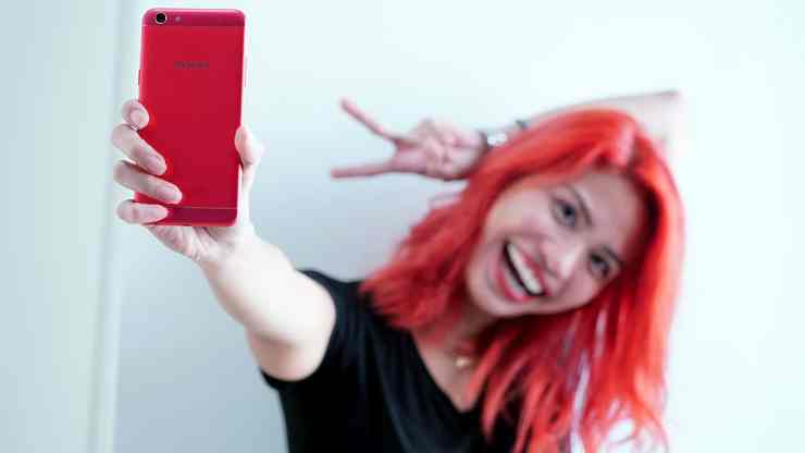 Red haired girl having with the Red OPPO F3