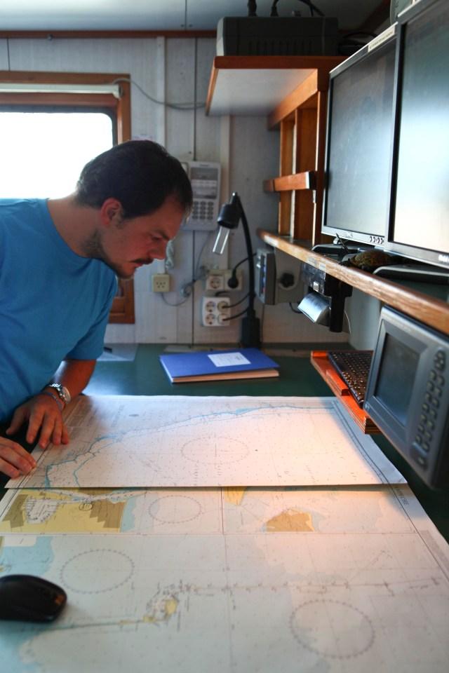 """El segundo oficial hace calculos en los mapas para determinar que tan peligroso puede ser salir a navegar en las """"zodiac"""""""