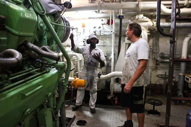 El segundo y tercer ingeniero intercambian palabras para realizar una tarea en el cuarto de máquinas