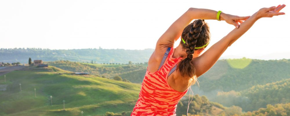 young fit woman against scenery of Tuscany stretching