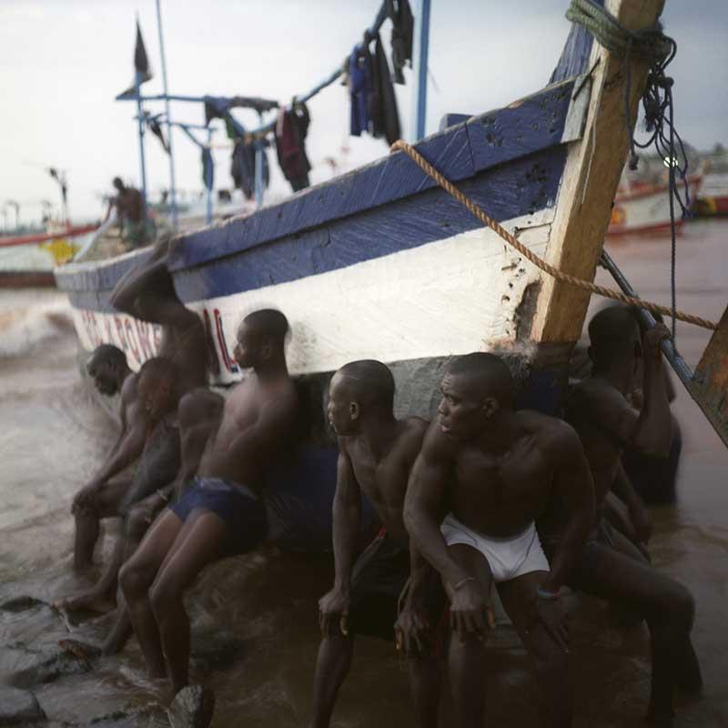 Garçons soulevant un bateau