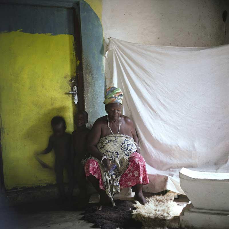 Grand-mère avec ses petits-enfants, dans la pièce où elle pratique la sorcellerie.