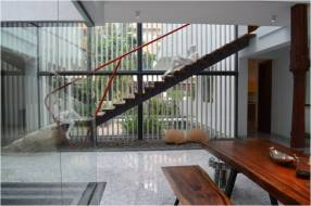 A bold red handrail and expressive sculptures make the staircase interesting