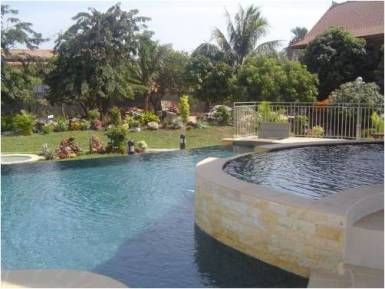 Kids pool overflowing in main pool which seems overflow into landscaped garden