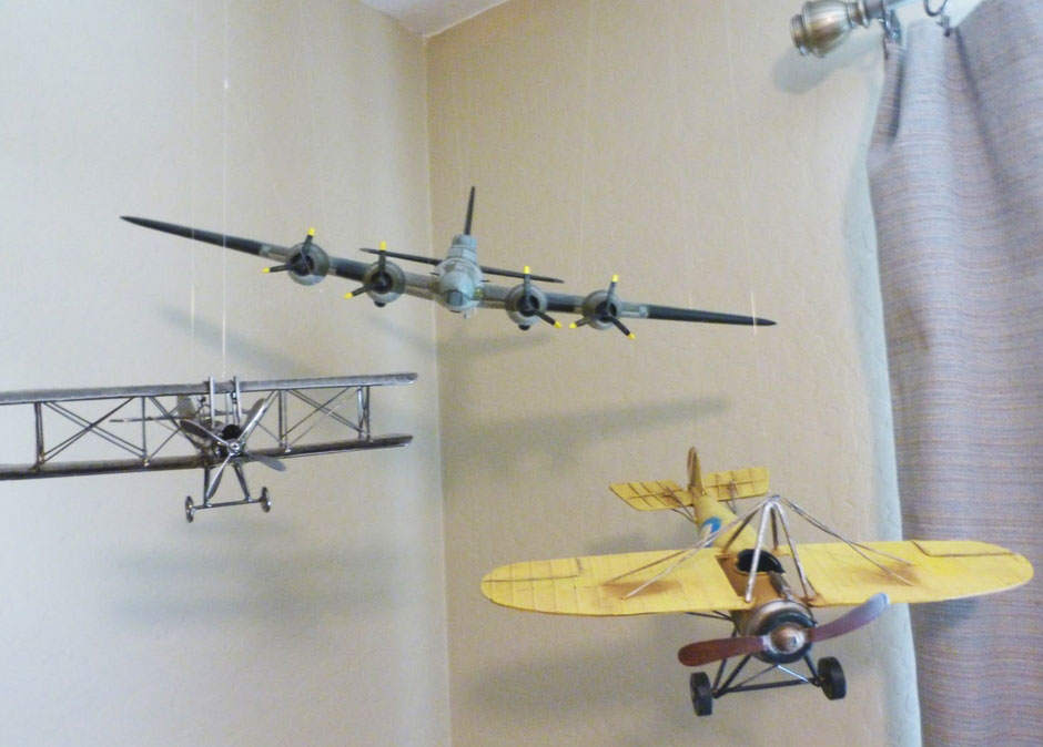 3 airplanes hang from the ceiling for use as a mobile in a baby room