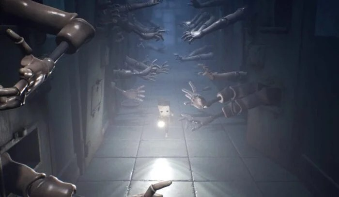 Mono running down a hall filled with arms grabbing in Little Nightmares 2