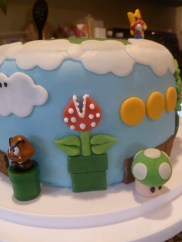 side view of mario cake showing goomba, 1-up, coins