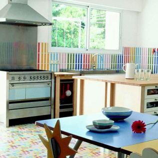 Cocina con mesa y bols. Azulejos combinando los colores del arco iris.