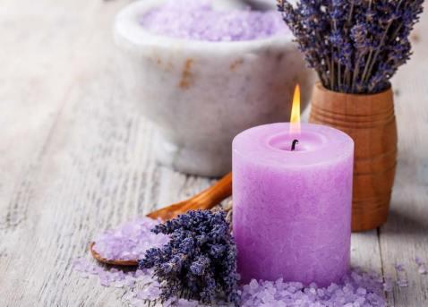 Vela en color lila y con un ramillete de lavanda y sales aromáticas.