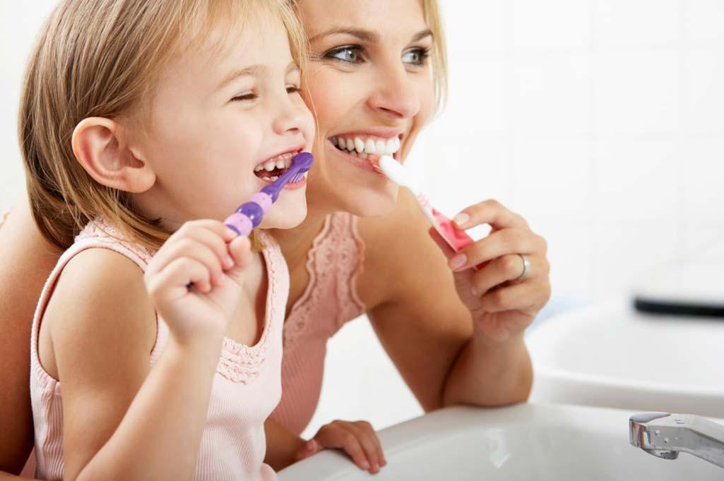 Madre e hija lavándose los dientes juntas en un cuarto de baño seguro para niños.